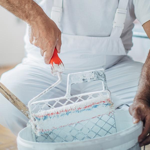 Pracownik zwałkiem malarskim wdłoni